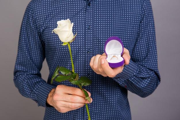 Close-up foto van man met witte roos gaat huwelijksaanzoek doen