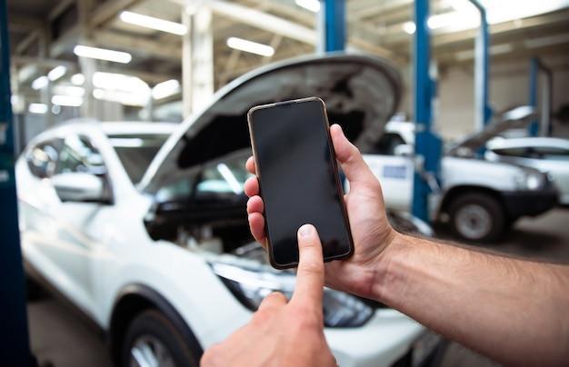 Close-up foto van mannelijke handen met een leeg scherm van smartphone op de achtergrond van autoservicecentrum met het repareren van auto's