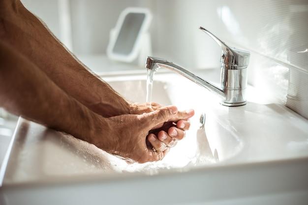 Close-up foto van mannelijke handen met zeep in de wasbak. veiligheidsprocedure, pandemie, antibacterieel.
