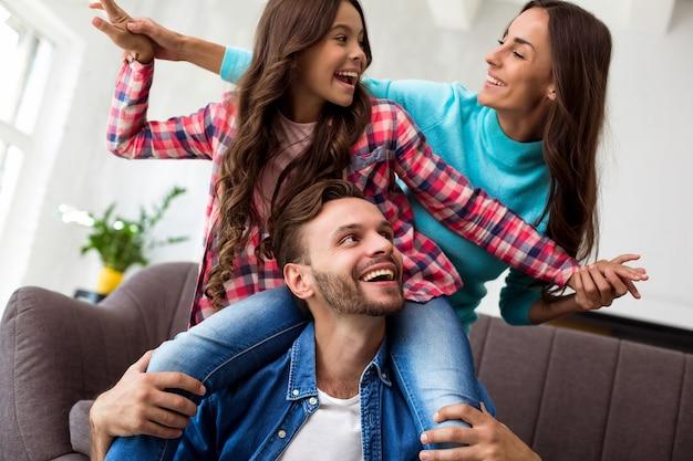Close-up foto van moeder, vader en hun dochter die samen poseren voor een gezamenlijke foto in hun stijlvolle woonkamer, knuffelend met een stralende glimlach