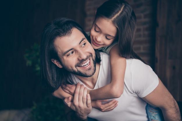 Close-up foto van mooi klein schattig meisje en knappe jonge papa knuffelen piggyback dromerige glimlach weekend tijd huiselijke huis kamer binnenshuis doorbrengen
