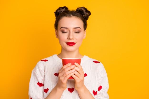 Close-up foto van mooie dame met warme koffie drank beker ogen gesloten genieten van mooie geur emotionele slijtage harten patroon wit rode trui Premium Foto