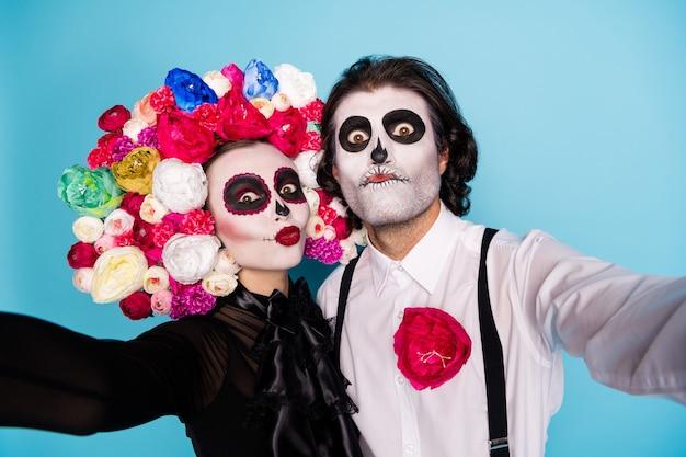 Close-up foto van mooie demon paar man dame omhelzing nemen selfie grappige grap buurman dragen zwarte jurk dood kostuum suiker schedel rozen hoofdband bretels geïsoleerde blauwe kleur achtergrond