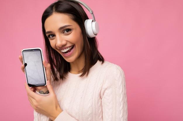 Close-up foto van mooie gelukkig lachende jonge vrouw dragen stijlvolle casual outfit geïsoleerd op achtergrond muur houden en tonen van mobiele telefoon met lege display voor mockup dragen witte bluetooth hij