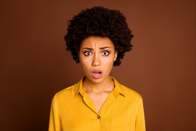 Close-up foto van mooie mooie donkere huid gekrulde dame met open mond benadrukt moet werken in het weekend slecht vreselijk nieuws stupor gele shirt geïsoleerde bruine kleur dragen