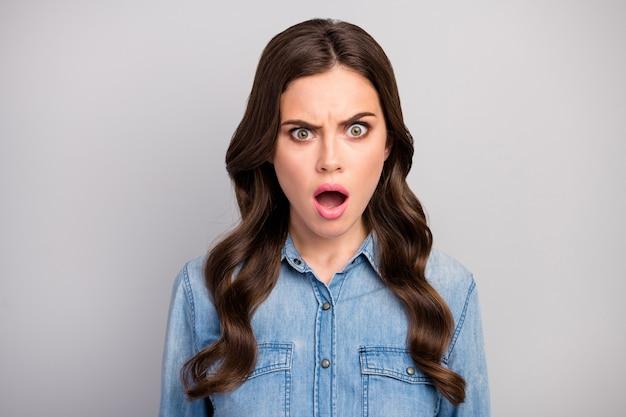 Close-up foto van mooie mooie krullende dame open mond luisteren slecht vreselijk nieuws ontevreden situatie problemen dragen casual jeans kleding geïsoleerde grijze kleur