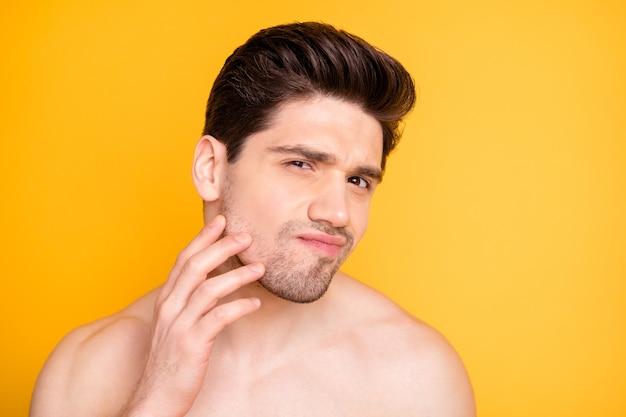 Close-up foto van onrustige man die zijn gezichtshuid controleert op zoek naar spiegel met borstelharen geïsoleerde levendige kleurenmuur
