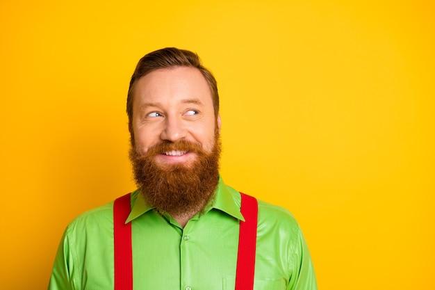 Close-up foto van opgewonden grappige roodharige kerel toothy glimlachen kijken kant lege ruimte denken over gekke truc dragen groen shirt rode bretels geïsoleerde levendige kleuren