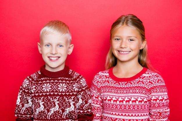 Close-up foto van opgewonden kinderen in traditionele x mas gebreide kleding, poseren, staande geïsoleerd op rode ruimte, klaar voor feest, eenheid en saamhorigheid. heilige tijd van het jaar!