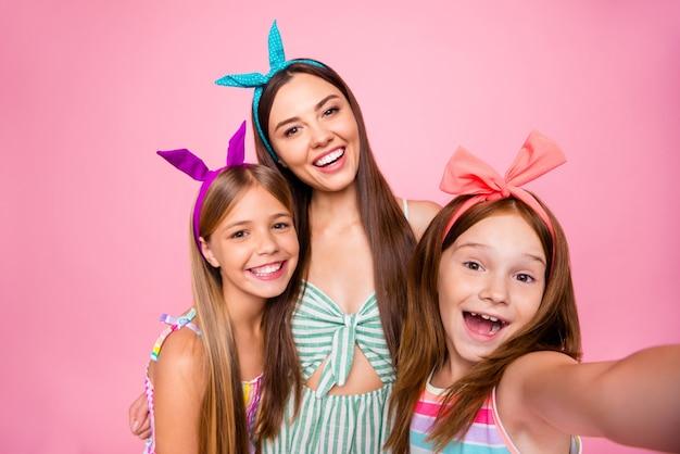 Close-up foto van opgewonden meisjes die zelfportret maken, gekleed in heldere jurken die over roze achtergrond worden geïsoleerd