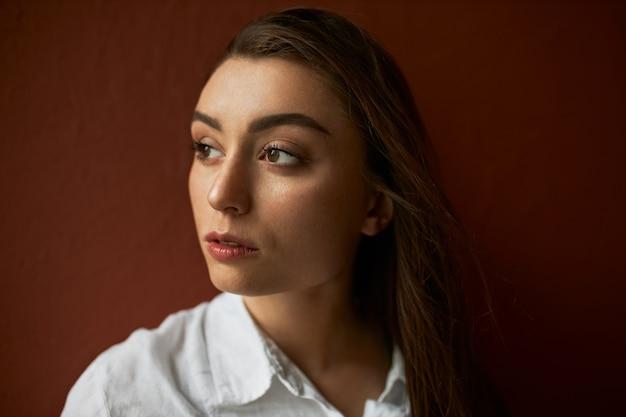 Close-up foto van peinzende doordachte ernstige jonge vrouw met lang bruin haar en perfect schone huid wegkijken