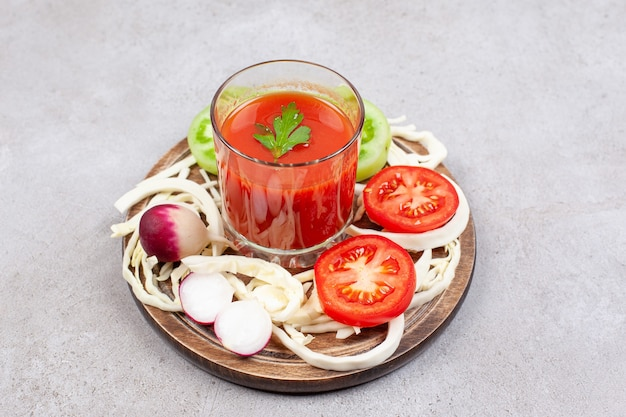 Close-up foto van plakjes tomaat met radijs en kool met saus op een houten bord.