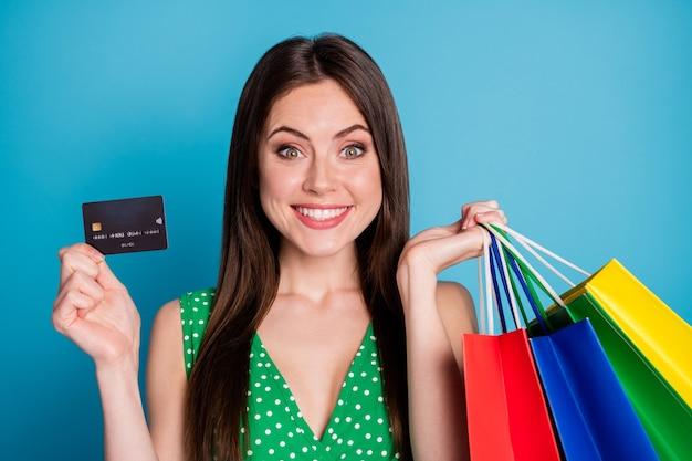 Close-up foto van positief vrolijk meisje geniet van winkelen, houd veel tassen aan raden betalen creditcard dragen stijl stijlvolle trendy tank-top geïsoleerd over blauwe kleur achtergrond