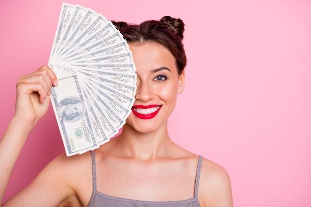 Close-up foto van positieve meisje houden geld ventilator verbergen half gezicht miljoen dollar ze winnen loterij dragen mooie kleding geïsoleerd over roze kleur
