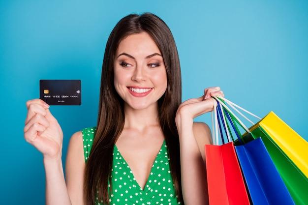 Close-up foto van positieve vrolijke meid houd blik creditcard betaal veel tassen dragen stijl stijlvol trendy hemd geïsoleerd over blauwe kleur achtergrond