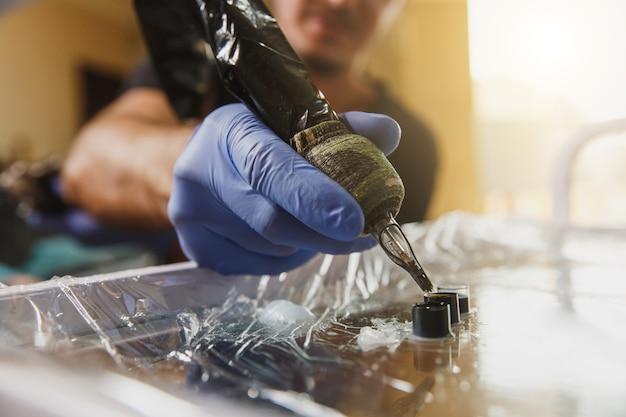Close-up foto van professionele tattoo-artiest wint in de tattoo-machine met zwarte inkt en maakt een foto op de arm van een jonge man
