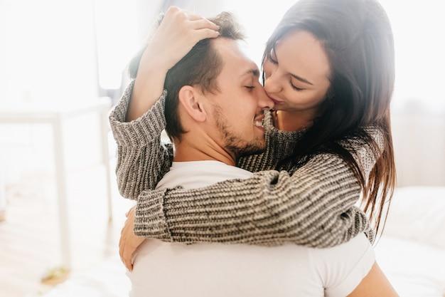Close-up foto van romantische dame in grijze kleding omarmen vriendje op lichte achtergrond