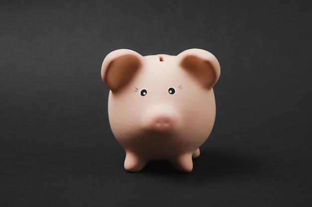 Close-up foto van roze spaarvarken geïsoleerd op zwarte muur achtergrond. geldaccumulatie, investeringen, bank- of zakelijke diensten, rijkdomconcept. kopieer ruimte reclame mock-up.