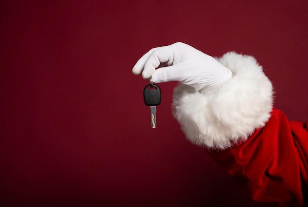 Close-up foto van santa claus hand in witte handschoen met een nieuwe sleutel