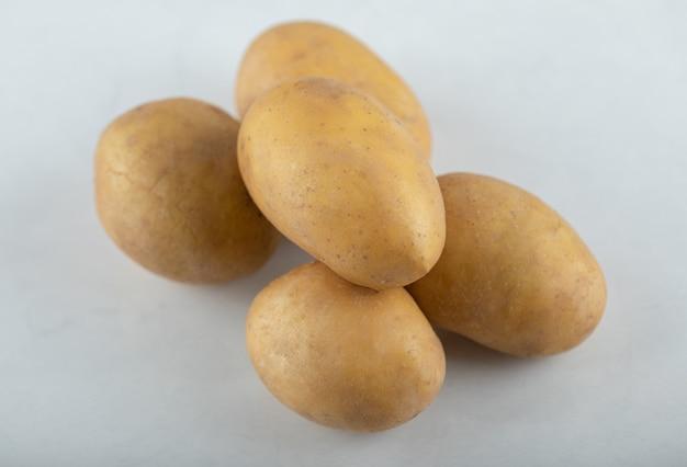 Close-up foto van stapel aardappelen op witte achtergrond.