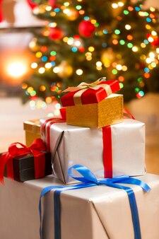 Close-up foto van stapel geschenkdozen onder de kerstboom in de woonkamer