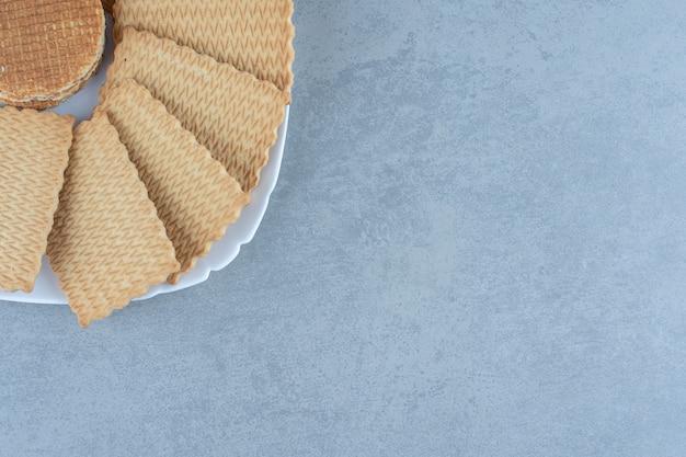 Close-up foto van stapel wafel en koekjes op plaat.