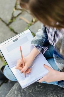 Close-up foto van student die essay schrijft in haar notitieblok en buiten zit sitting