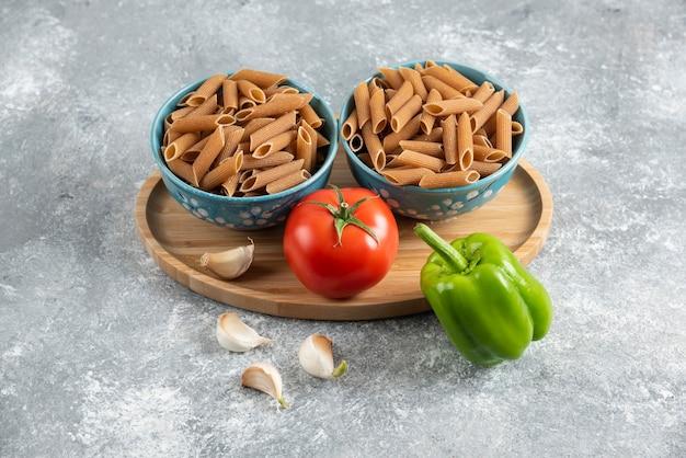 Close-up foto van twee kom vol met bruine pasta en verse biologische groenten.