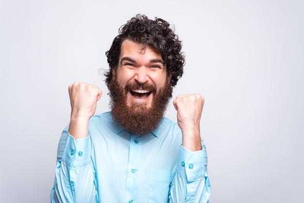 Close-up foto van verbaasd bebaarde hipster man in casual vieren met armen omhoog.
