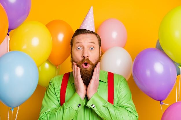 Close-up foto van verbaasde gekke heer geniet van verjaardagsfeestje cadeau krijgen cadeau onder de indruk schreeuw wow draag gestippelde kegelmuts goede look kleding over glans kleur