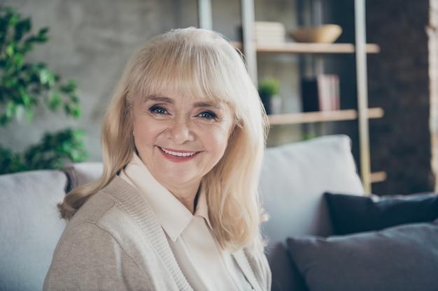 Close-up foto van verbazingwekkende blonde schattige oude oma huiselijke goed humeur toothy stralend glimlachend vrolijke zitcomfort sofa divan woonkamer binnenshuis