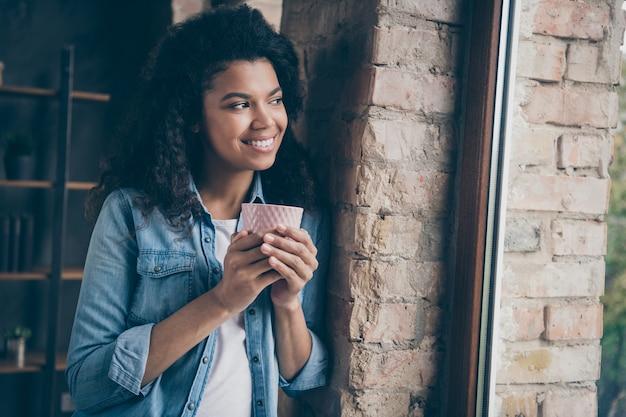 Close-up foto van verbazingwekkende donkere huid krullend dame bedrijf warme koffie drinken op zoek naar raam leunende bakstenen muur dragen casual denim outfit moderne appartementen binnenshuis
