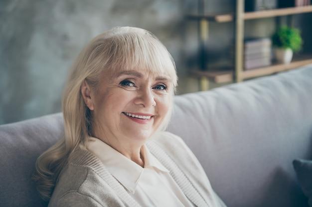 Close-up foto van verbazingwekkende schattige oude oma huiselijke goed humeur toothy stralend glimlachend zitcomfort sofa divan woonkamer binnenshuis