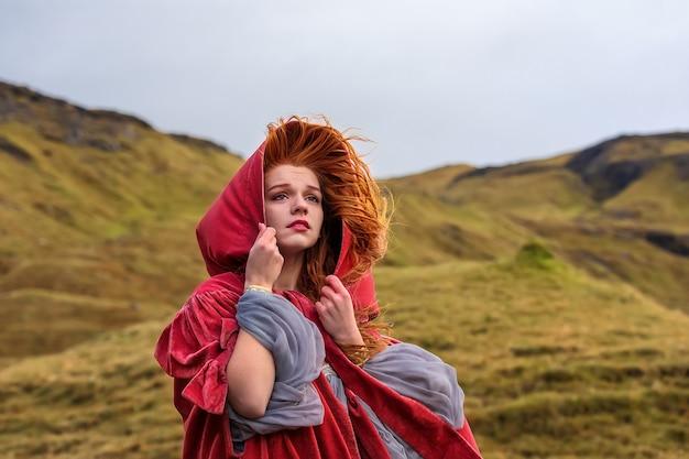 Close-up foto van verdrietig meisje in ouderwetse kleding met een rode mantel. faeröer
