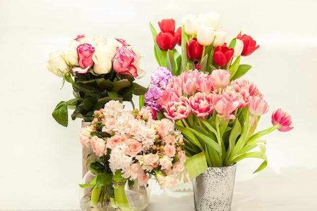 Close-up foto van verschillende verse snijbloemen in vazen tegen wit