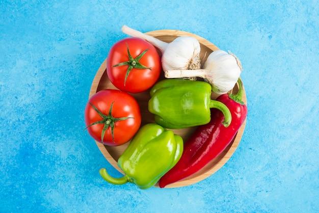 Close-up foto van verse biologische groenten op een houten bord over grijze tafel.
