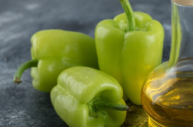 Close-up foto van verse biologische paprika's met fles olie over grijze achtergrond.