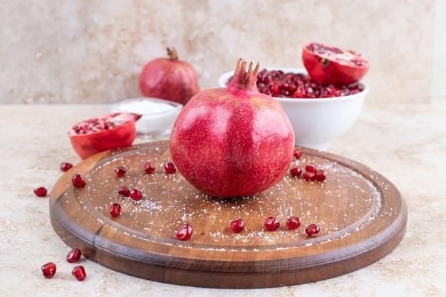 Close-up foto van verse granaatappel op een houten bord.