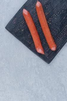 Close-up foto van verse salami bladeren op zwarte snijplank.