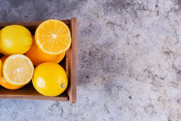 Close-up foto van verse, sappige citroenen in houten doos.