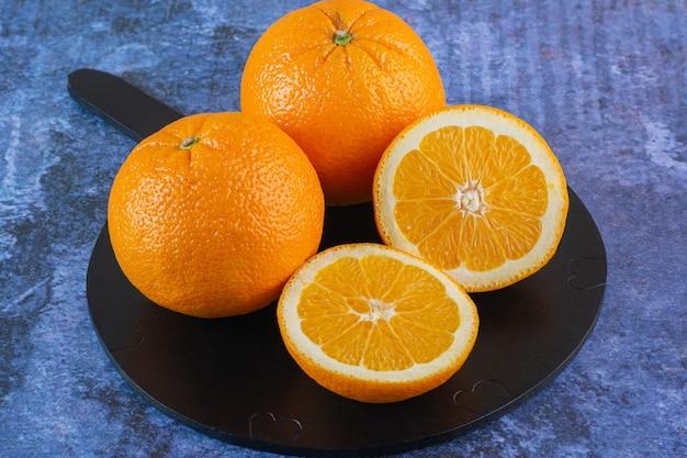 Close-up foto van verse sinaasappelen op een zwarte bord.