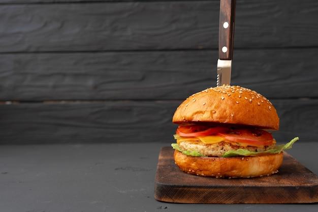 Close-up foto van verse smakelijke hamburger tegen zwarte achtergrond