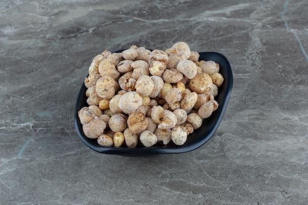 Close-up foto van verse zelfgemaakte snoepjes in zwarte kom.