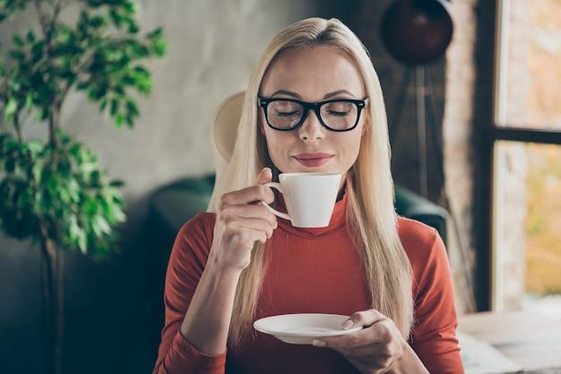 Close-up foto van vreedzame werknemer vrouw in oranje coltrui rust ontspannen houden witte koffiekopje geur aroma genieten in loft kantoor werkstation rode coltrui