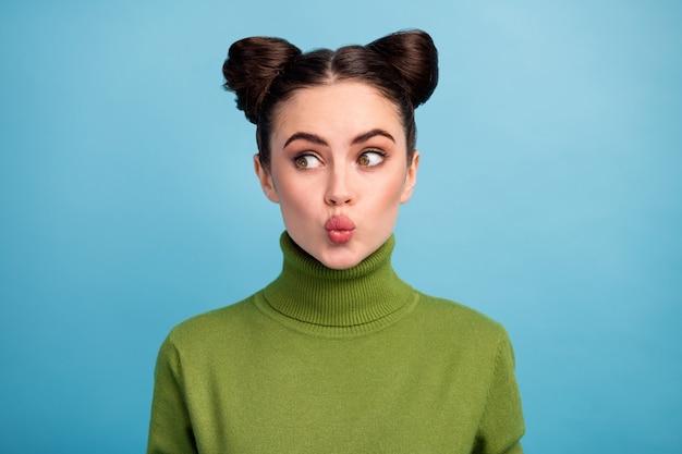 Close-up foto van vrij aantrekkelijke dame tiener twee schattige broodjes luchtkussen verzenden kijken kant lege ruimte dragen groene warme coltrui geïsoleerde blauwe kleur muur