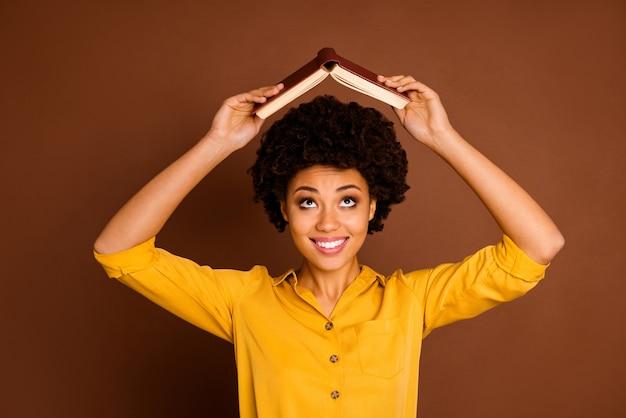 Close-up foto van vrij grappige donkere huid dame open boek huiswerk onder hoofd gek rond kinderlijke stemming dragen gele shirt geïsoleerde bruine kleur