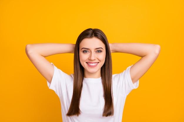 Close-up foto van vrij kalm dame goed humeur dutten denken armen achter het hoofd opgetogen brede glimlach dragen casual wit t-shirt geïsoleerde levendige gele kleur muur