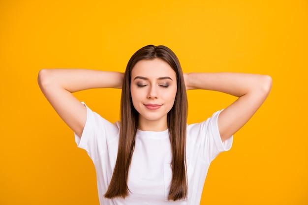Close-up foto van vrij rustige dame opgetogen goed humeur ogen gesloten dutten denken armen achter het hoofd dragen casual wit t-shirt geïsoleerd levendige gele kleur muur