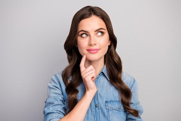 Close-up foto van vrij schattig krullend dame houden vinger op kin opzoeken lege ruimte dromer creatieve persoon dragen casual jeans kleding geïsoleerde grijze kleur