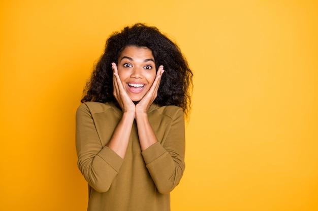 Close-up foto van vrij verbazingwekkende donkere huid dame luister ongelooflijk goed nieuws houd armen op wangen dragen casual pullover geïsoleerd op gele kleur achtergrond